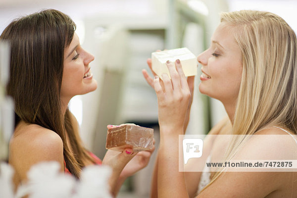 Women smelling candles in store
