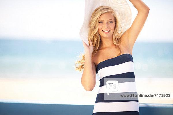 Frau mit Schlapphut am Strand