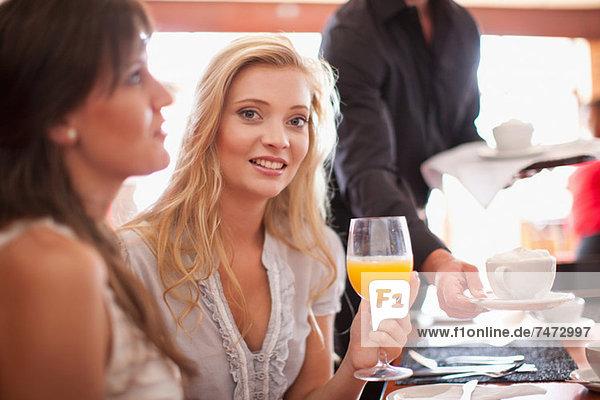 Frau mit Orangensaft im Café