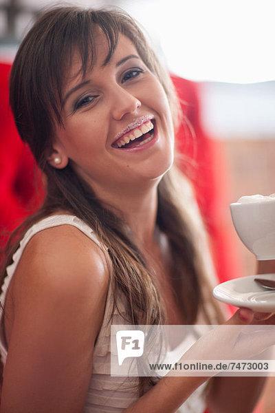 Frau mit Milchschnurrbart im Café Mund