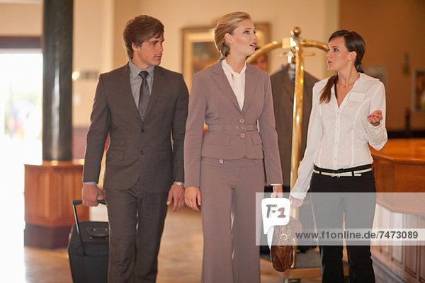 Geschäftsleute  die in der Hotellobby spazieren gehen