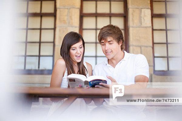 Paare lesen Reisebuch zusammen