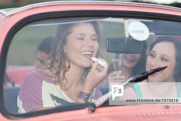 Frau mit Lippenstift im Cabriolet