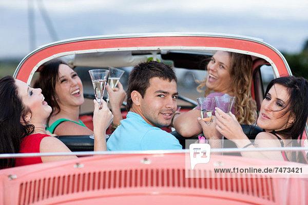 Freunde toasten im Cabriolet