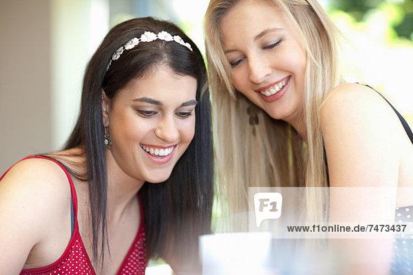 Lächelnde Frauen sitzen zusammen