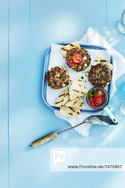 Grilled Burgers and Pita Bread on Tray with Spatula on Blue Wooden Table in Studio