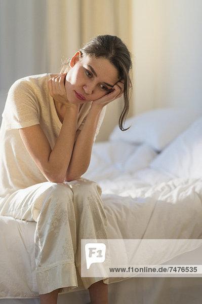 sitzend  Frau  Kopfschmerz  Bett  jung