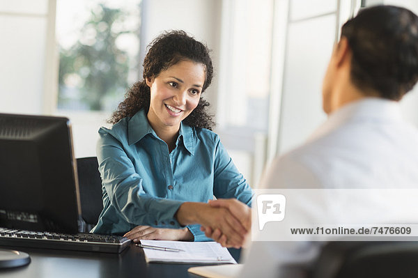 Woman shaking hand with man at desk