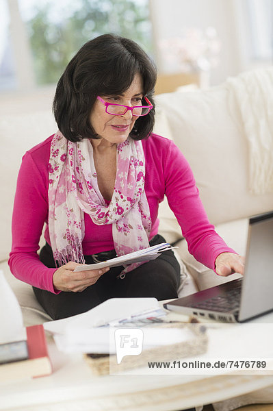 Portrait of senior woman sitting in living room with laptop