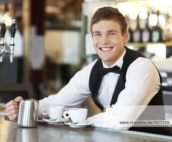 Portrait of barista holding milk jug
