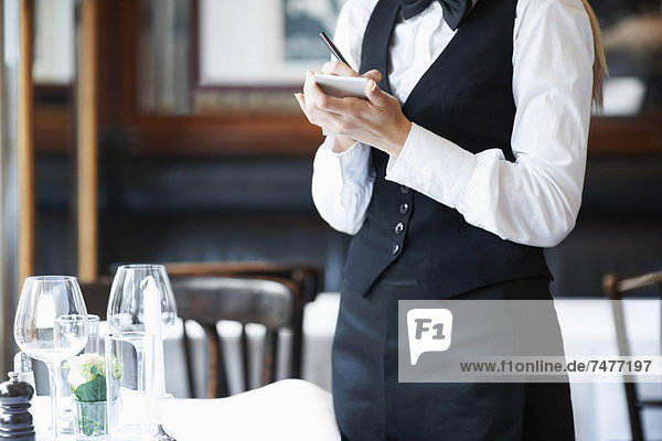 Young waitress taking order