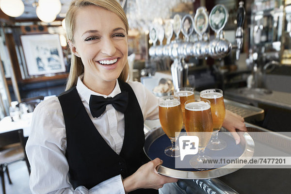 Portrait of young woman holding tray with beer glasses