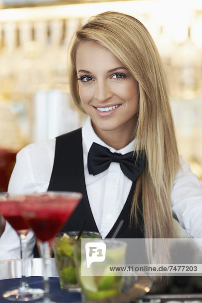 Portrait of female bartender holding tray with cocktails