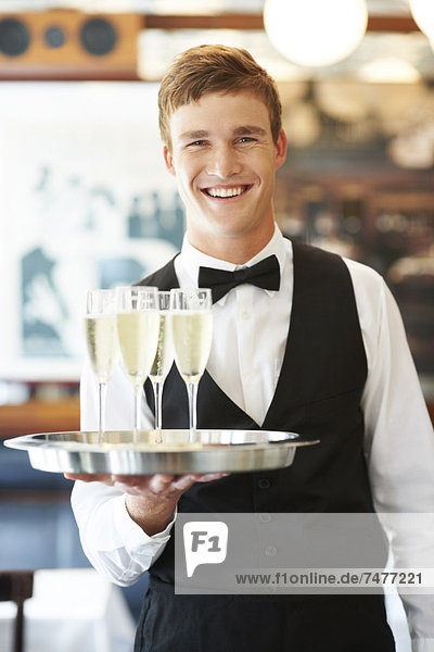 Portrait of waiter holding champagne flutes on tray