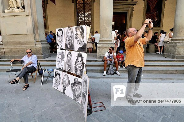 Tourists taking a photograph and cartoonist. Florence  Tuscany. Italy.