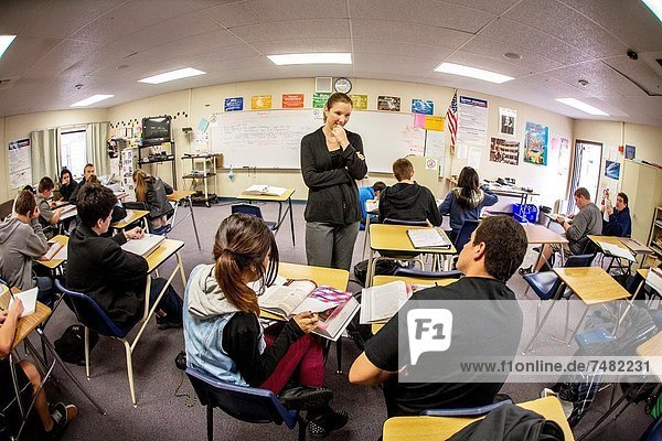 A California high school English teacher assists her students´ comprehension during a reading exercise using a literary anthology