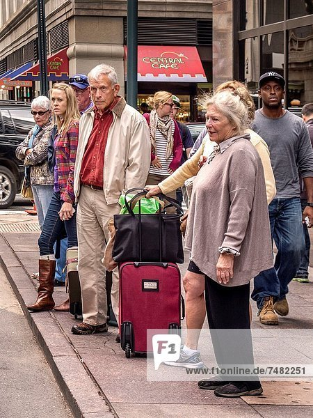 A grim-looking group of newly-arrived travelers wait on the sidewalk outside New York´s Grand Central Station with their luggage for taxi transportation