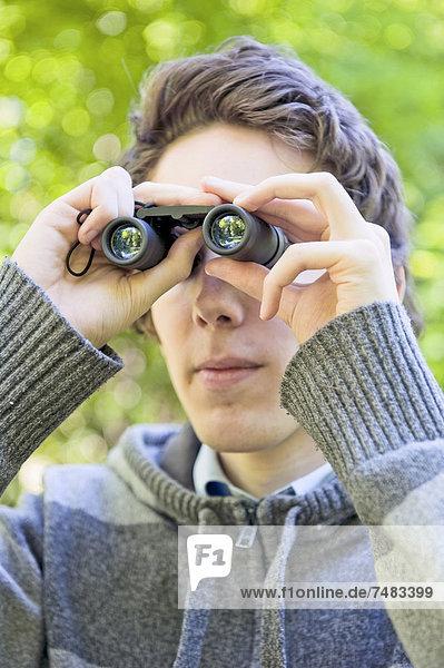Junger Mann sieht durch ein Fernglas  Vogelbeobachtung  Schweden  Europa