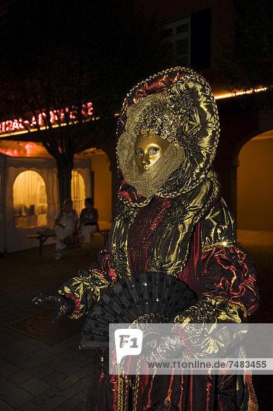Person mit goldener Barockmaske  Fächer und prunkvollem Kostüm bei Nacht  Venezianische Messe Ludwigsburg  Baden-Württemberg  Deutschland  Europa