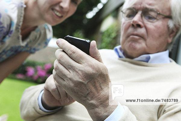 Junge Frau erklärt Senior die Bedienung eines Smartphones
