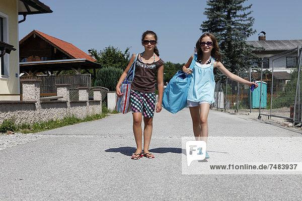 Zwei Mädchen  11 Jahre  beim Tragen von großen Taschen  Ísterreich  Europa