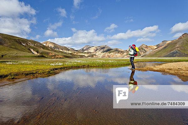 Spiegelung einer jungen Frau in einem Teich  Landmannalaugar  Island  Europa