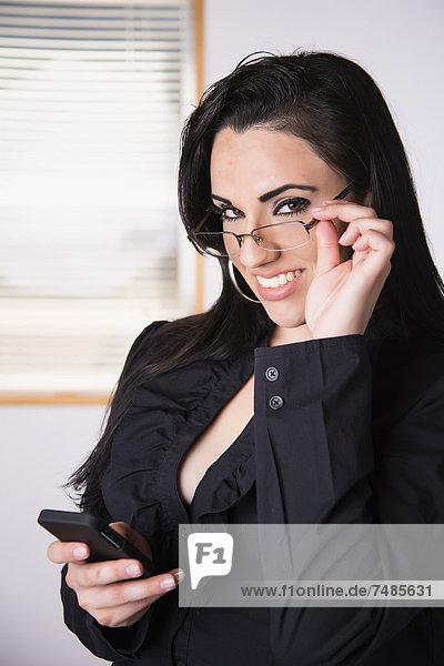 USA  Texas  Geschäftsfrau mit Smartphone  lächelnd  Portrait