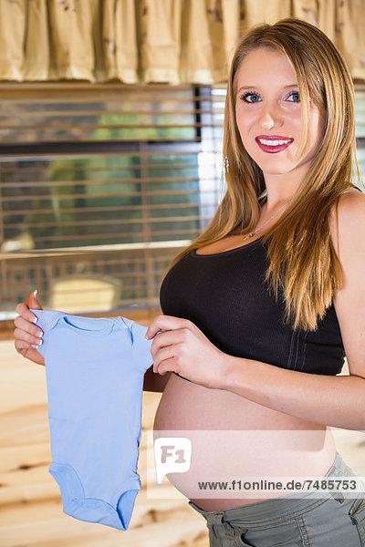 USA  Texas  Schwangere junge Frau mit Babykleidung