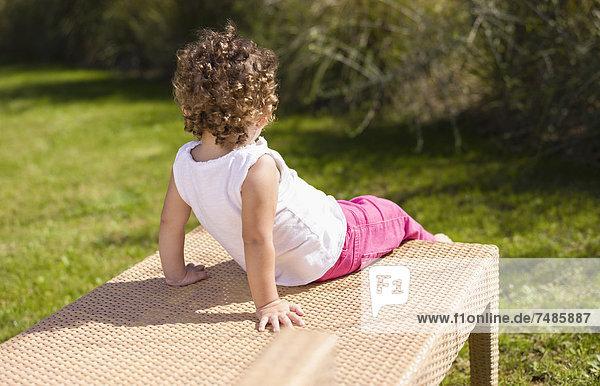 Spanien  Mädchen auf Bank sitzend
