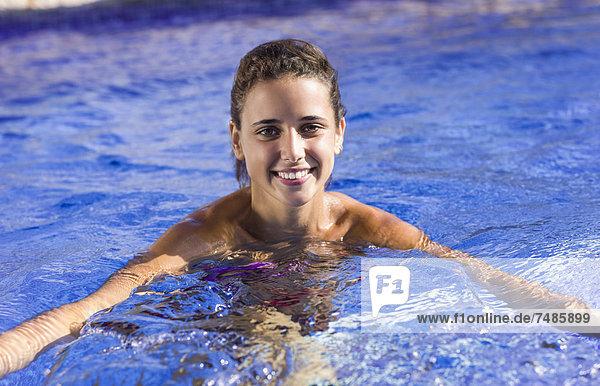 Spanien  Teenagerin im Pool schwimmend  lächelnd  Portrait
