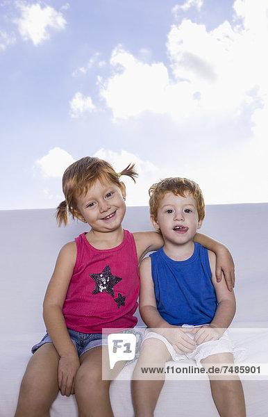 Spanien  Junge und Mädchen auf weißer Couch sitzend  lächelnd