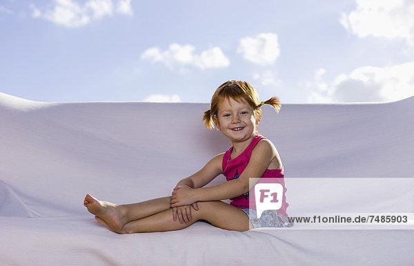 Spanien  Mädchen auf weißer Couch sitzend  lächelnd  Portrait
