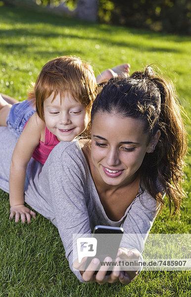 Spanien  Teenage Mädchen und Mädchen mit Smartphone auf Gras