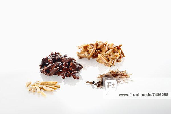 Vielfalt an Schokolade mit Mandelstücken auf weißem Grund