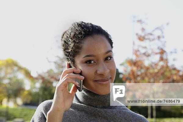 Junge Frau spricht auf dem Smartphone