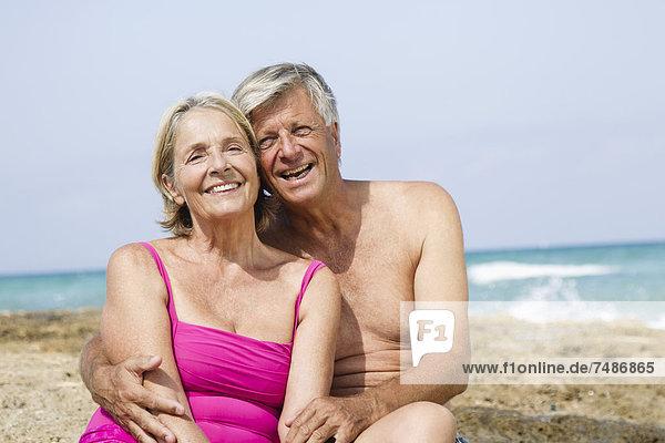 Spanien  Seniorenpaar auf Felsen am Strand sitzend  lächelnd