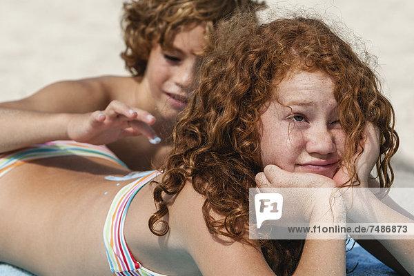 Spanien  Bruder auf dem Rücken der Schwestern mit Sonnencreme