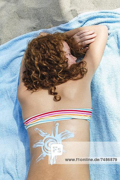 Spanien  Mädchen mit Design von Sonnencreme auf Strandtuch liegend