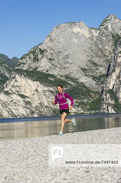 Italien  Mid adult woman jogging am Gardasee