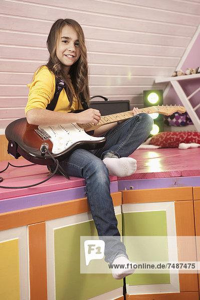 Girl playing guitar  smiling  portrait