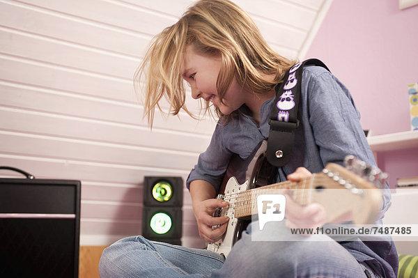 Girl playing guitar  smiling