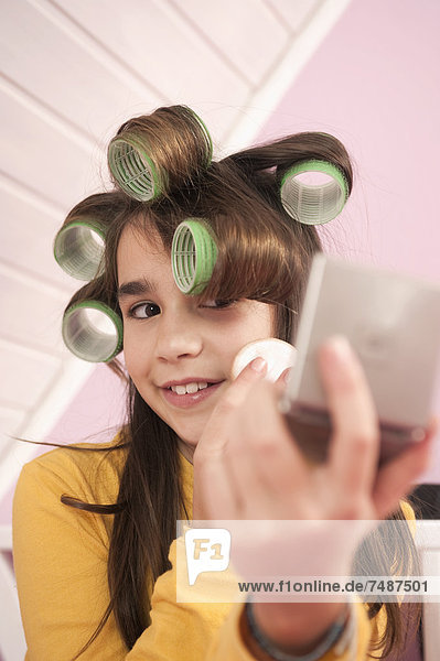 Girl with hair roller putting make up and looking in hand mirror