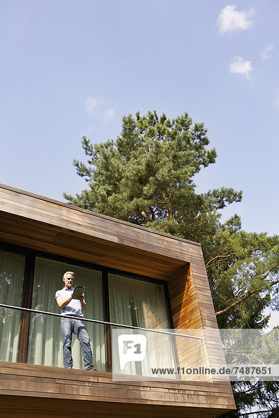 Erwachsener Mann auf dem Balkon stehend und mit Tablette