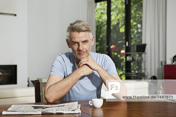 Erwachsener Mann am Tisch sitzend  Portrait