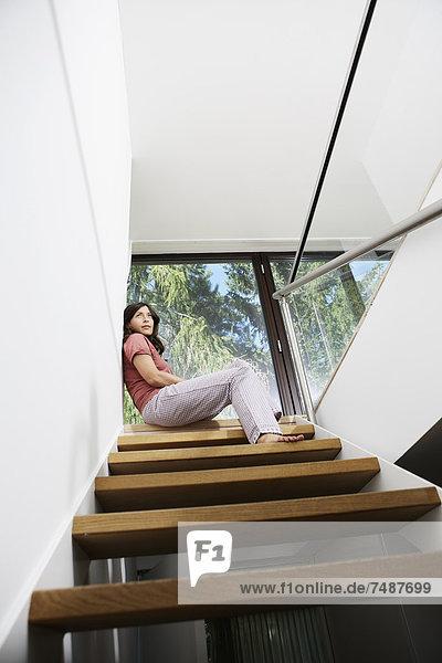 Reife Frau beim Tagträumen auf der Treppe