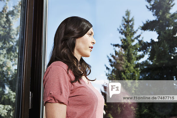 Reife Frau schaut durchs Fenster