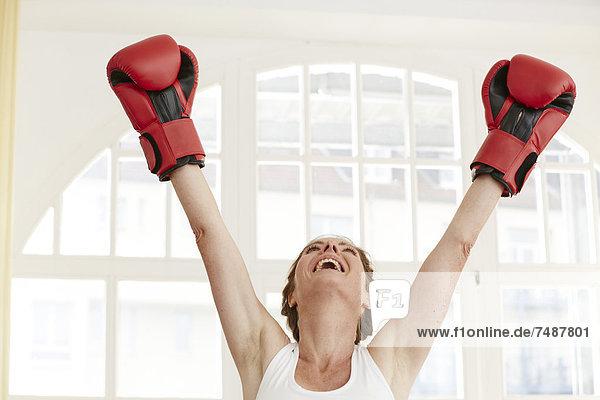 Reife Frau mit Boxhandschuhen