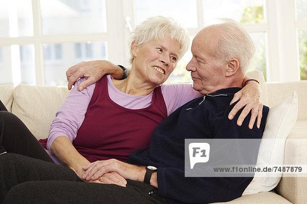 Deutschland  Düsseldorf  Seniorenpaar entspannt zu Hause  lächelnd