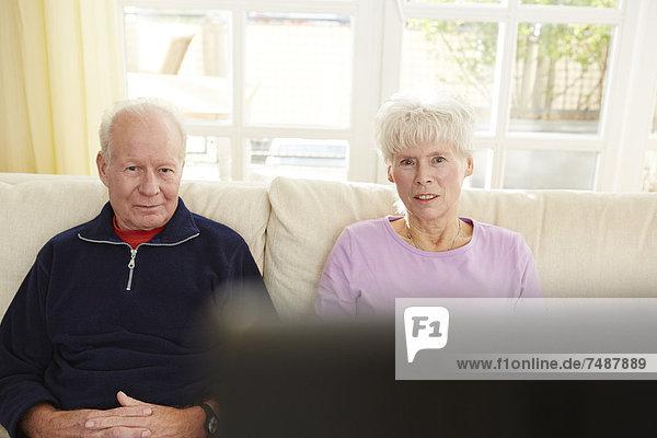 Deutschland  Düsseldorf  Seniorenpaar beim Fernsehen und Entspannen zu Hause