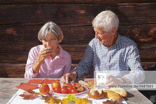Deutschland  Bayern  Seniorenpaar beim Essen auf der Berghütte
